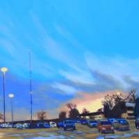 bluish sky over golden parking lot lit by last rays of sun